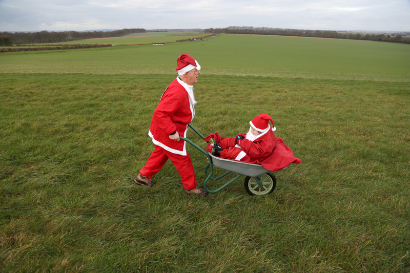 Chris Isaacs gives his grandson a push in the Great Santa fn run at Badbury Rings