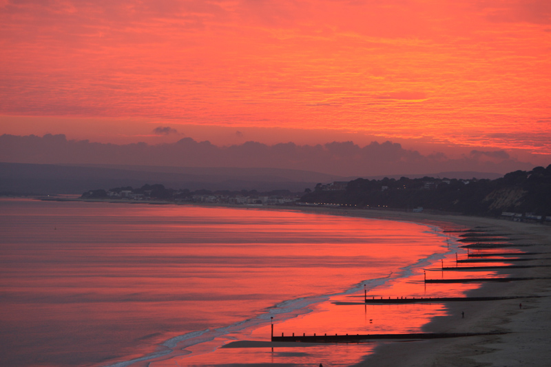 Red sky at night - Sunset casts a striking red glow along the seafront and beach between Bournemouth and Poole.
