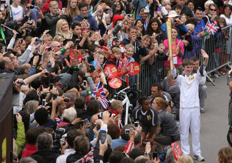 Charlie Rogers holds the Olympic torch aloft in Bournemouth gardens