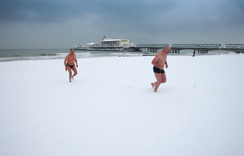 Charles Claydon and Honorius Micu walk across a snow covered Bournemouth beach after their morning swim in 2010