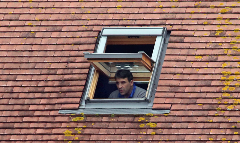 Poole Town manager Tommy Killick watches his team play from the window of a fan's house whilst serving a match ban