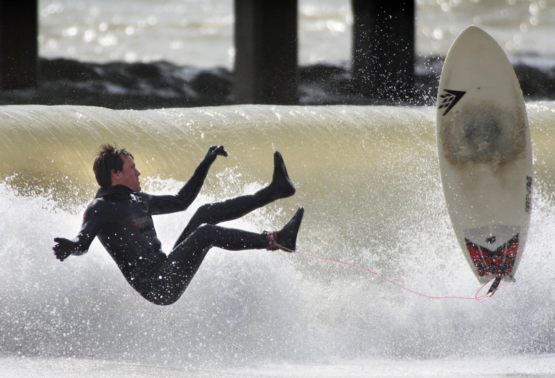 A surfer loses his board at Boscombe Pier