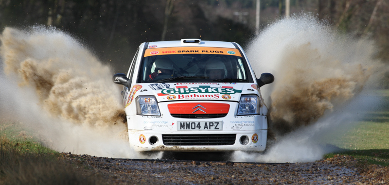 Richard Sykes and Simon Taylor go through the water splash at Somerley Park in the Rallye Sunseeker 2012 .